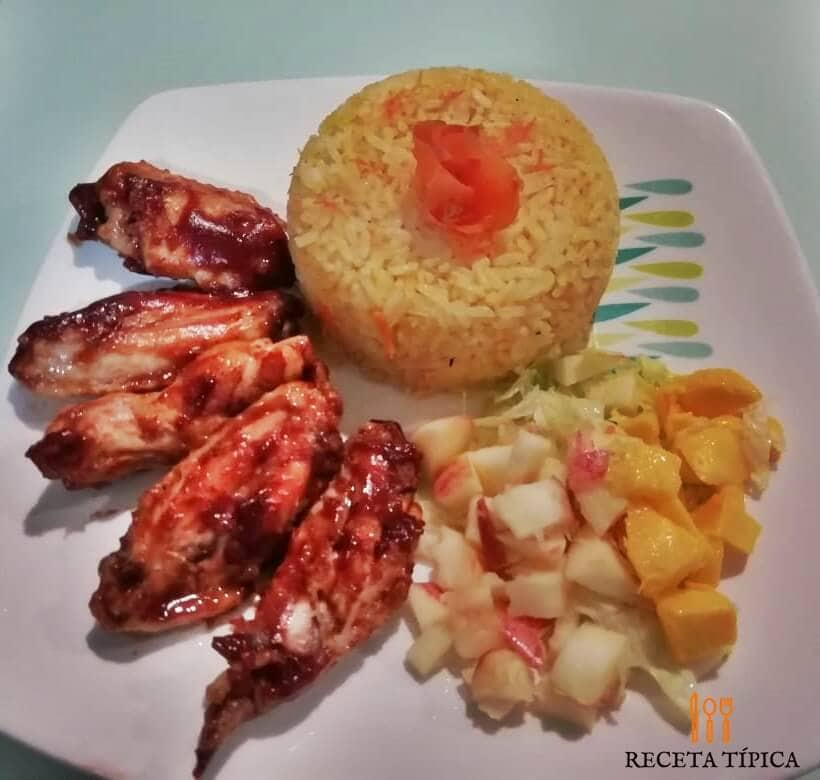 Dish with Barbecue chicken wings and yellow rice.